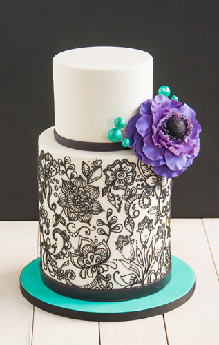 Black pipping on white birthday cake with big purple flower