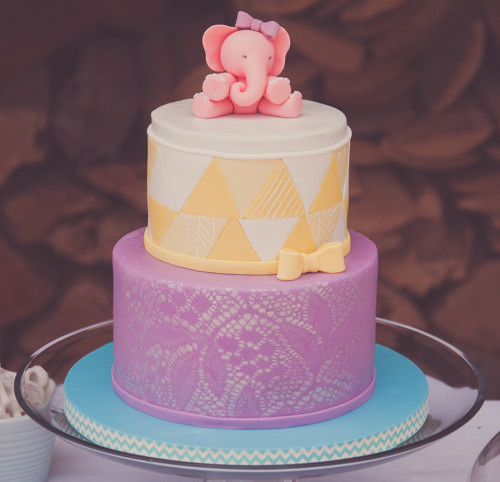 Pink elephant with bow on top of yellow and purple baby shower cake. Lace airbrush and quilting technique.