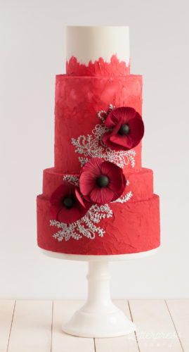 Red textured wedding cake with silver piping and three deep red sugar anemones
