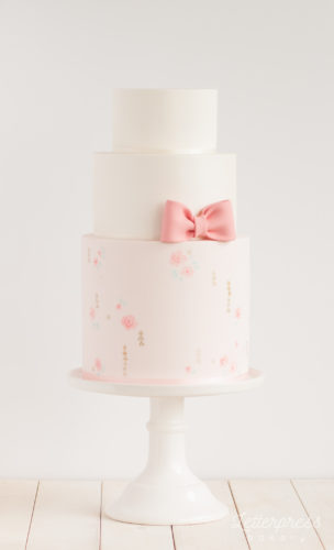 Three tier wedding cake, pink bow, hand painted pattern, triangles and roses, light pink, gold accents