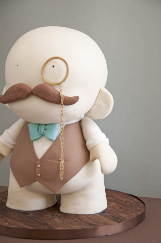 A dapper Mr. Munny cake with vest, bow tie, mustache and monocle.