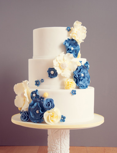 Pearl centres in blue and butter yellow flowers on a while wedding cake