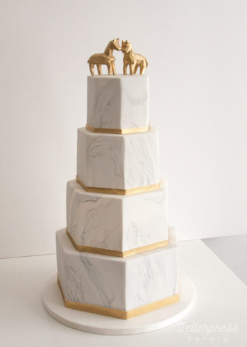 Geometric marble wedding cake with gold geometric horse cake toppers