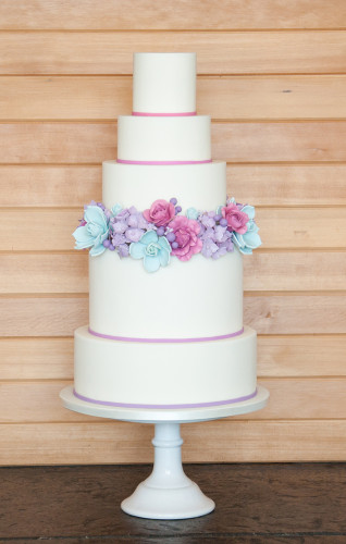 Sugar flowers in purple fusia and teal on five tier wedding cake