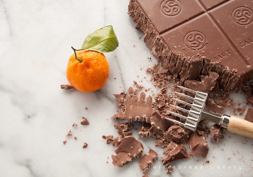 Chopping large block of milk chocolate with chocolate chopper. Chocolate and Tangerine for our Homer Stormtrooper Star Wars cake.