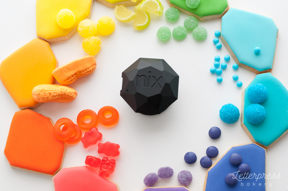 A rainbow of coloured cookies and candies with the Nix Sensor Pro in the middle