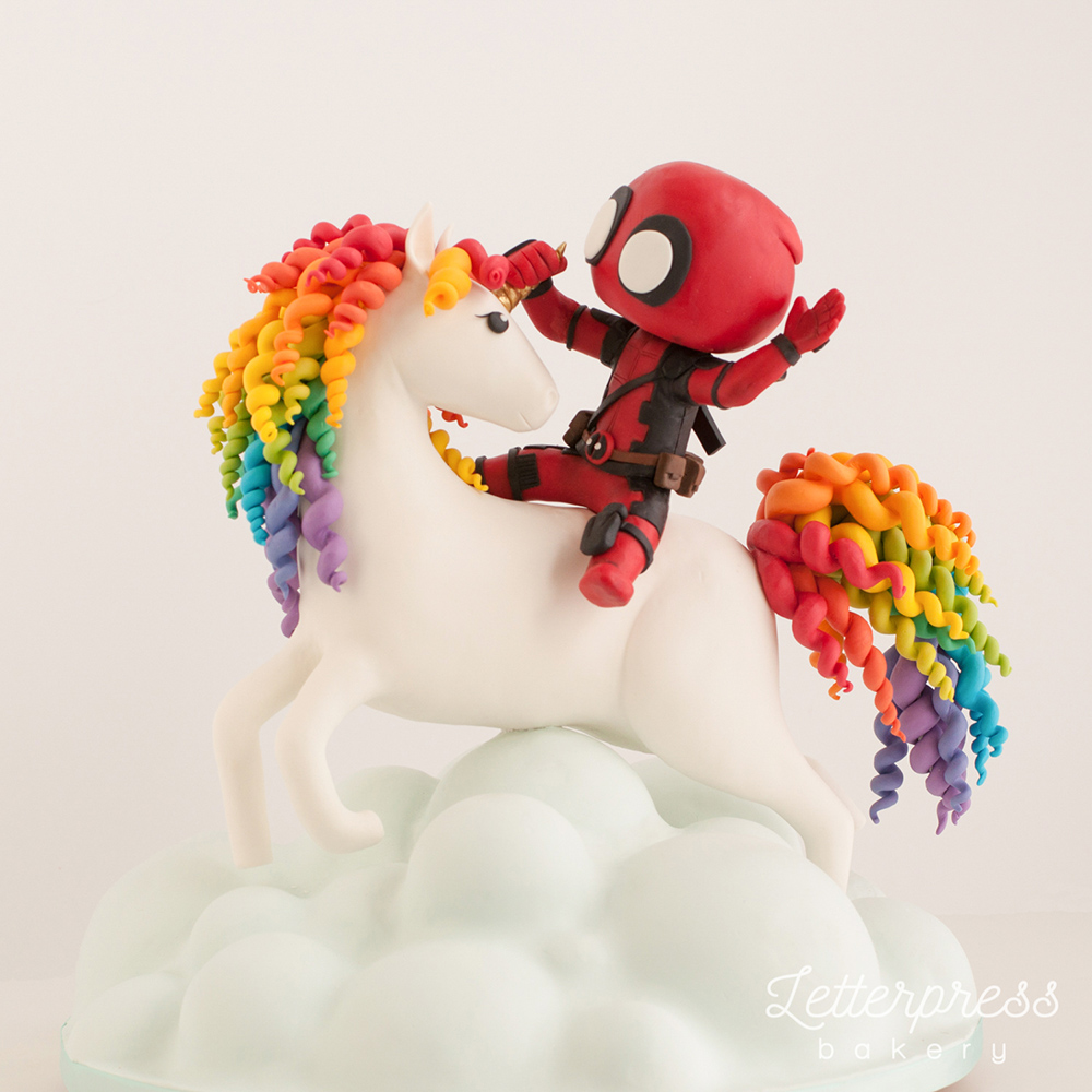 Deadpool cake riding a unicorn over a bunch of clouds
